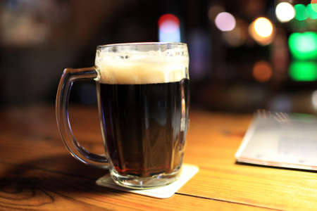 This is glass of dark beer on the wooden table in pub