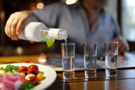 man pouring vodka in the pub in the evening