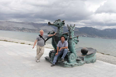 Two men posing with seahorse sculpture on the quay of Novorossiysk photo