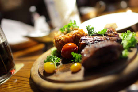 pub: pork ribs with vegetables on the wooden plate Stock Photo
