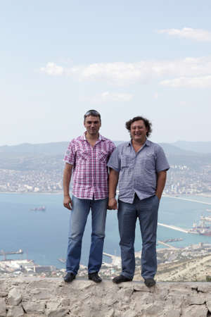 Two men posing on Tsemess Bay background in summer, Russia photo