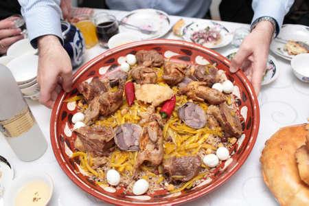 samarkand: Man holds samarkand pilau dish in uzbekistan Stock Photo