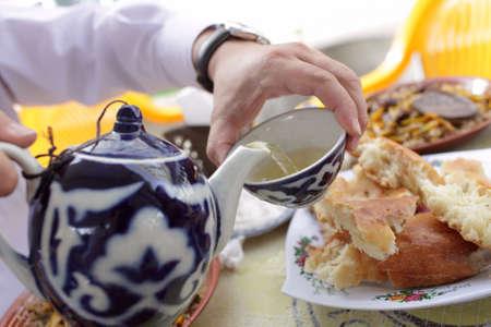 uzbekistan: Man pouring tea into cup from teapot, Uzbekistan, Tashkent Stock Photo