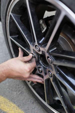 A man installs spare wheel to his car photo
