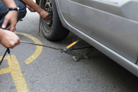 Man used a jack to lift his car and changed the wheel photo