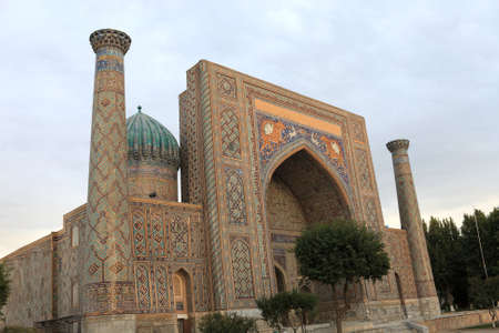 View of Sher Dor Madrasah. It was constructed from 1619-1636 in Samarkand, Uzbekistan. Ribbed domes on high towers soared over the two-storied facade on the sides of the front portal photo