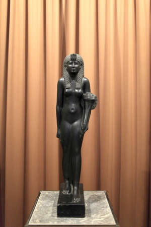 Black basalt statue of Cleopatra VII on the brown background. She was the last person to rule Egypt as an Egyptian pharaoh