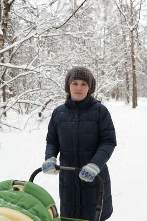 The woman holding a carriage in the winter forest photo