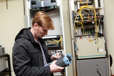 Telecom engineer adjusting reflectometer on the telecom site