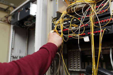 Telecom engineer connecting patch cord from multiplexer to ODF Redactioneel