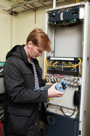 Telecom engineer holding reflectometer on the site