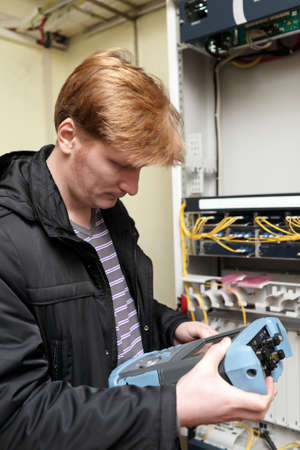 Telecom engineer looking at reflectometer on the telecom site