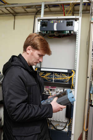 The engineer holding reflectometer on the telecom site