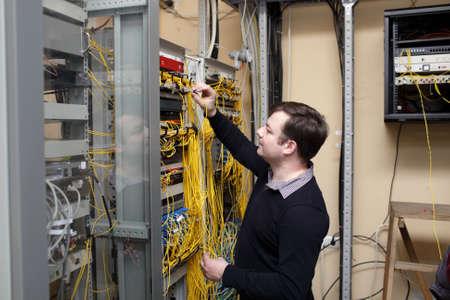 fibra óptica: El técnico de la red de conexión de fibra óptica en la sala de servidores