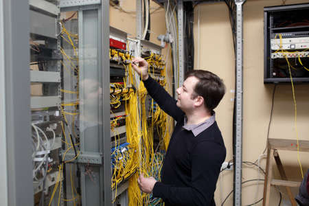 The network technician connecting fiber optic at server room photo
