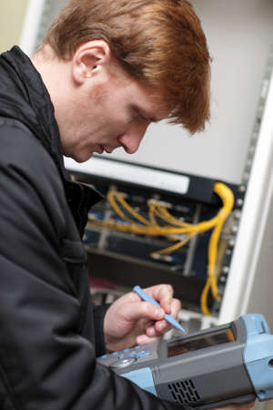 Technician adjusting telecom instrument at the server room Stock Photo