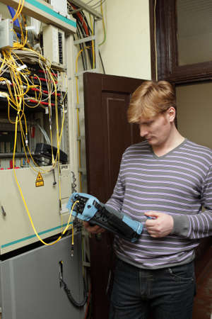 The technician measuring fiber optic at a server room photo
