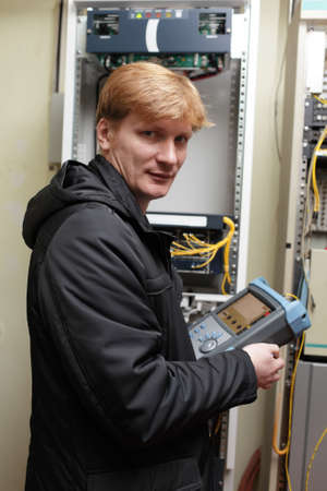 The technician posing with a instrument at the server room photo