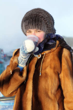 The woman drinking hot tea outdoor in winter, Siberia, Russia photo