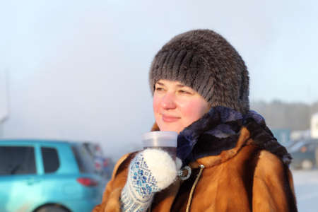 The woman holding cup of tea outdoor in winter, Siberia, Russia photo