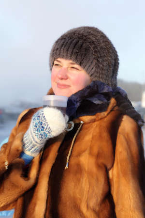 The woman posing with cup of hot tea outdoor in winter, Siberia, Russia photo