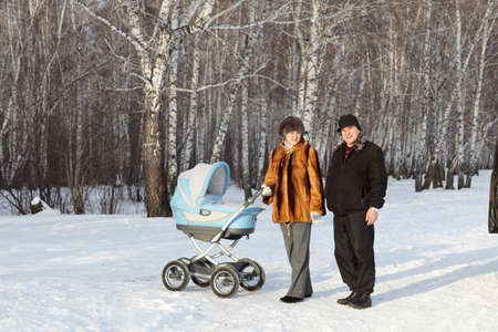 The family posing with baby carriage on the winter forest background, Siberia photo