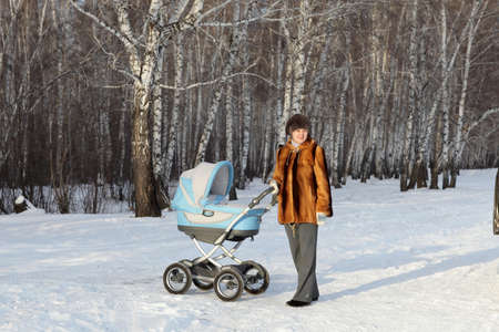 The mother posing with baby carriage on the winter forest background, Siberia photo