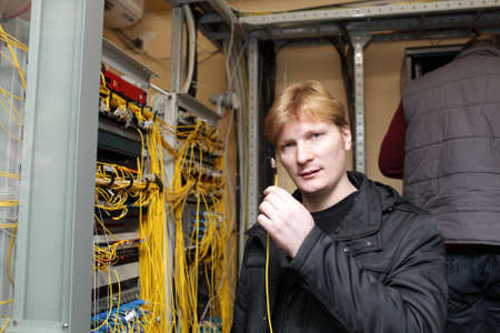 The technician showing fibre optic patch cord at a telecom site photo