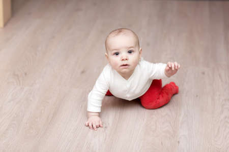 baby nursery: The baby waving his hand on a parquet at home