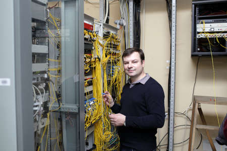 telecommunications equipment: Portrait of IT technician at a server room