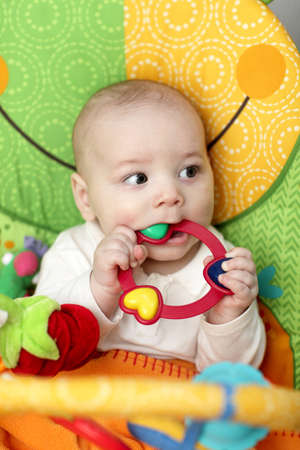 The baby boy biting a rattle ring at home Stock Photo - 12580558