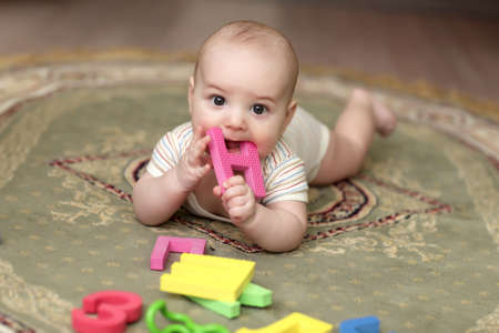 The baby boy biting a alphabet on a carpet at home photo