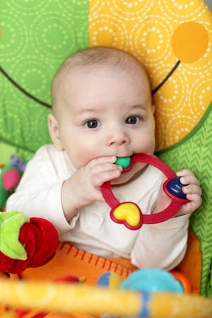 The baby playing with rattle ring at home photo