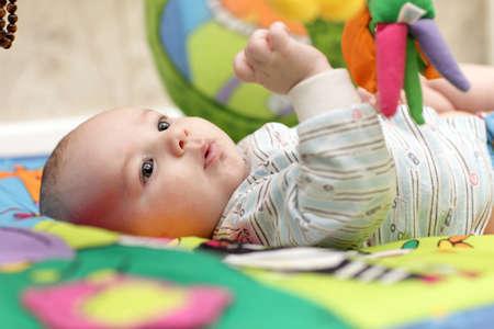 Retrato de muchacho serio bebé jugando en su casa