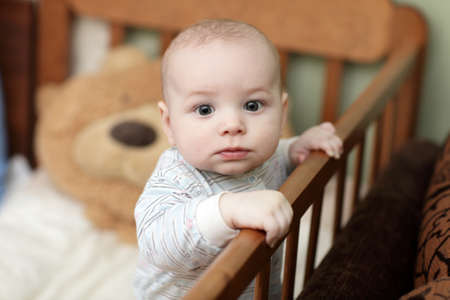 The pensive baby boy in cot at home photo
