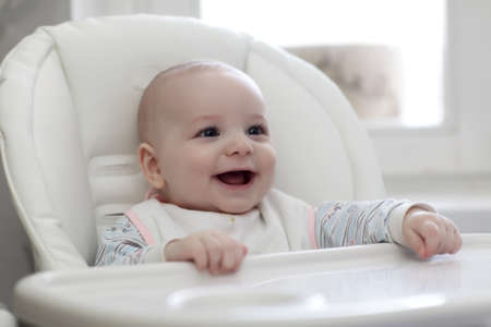 highchair: The happy baby laughing in highchair at home