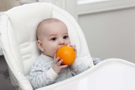 highchair: The baby boy biting orange in a highchair