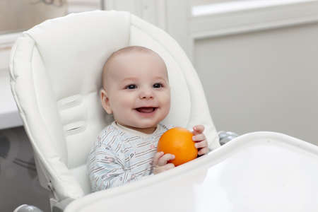 highchair: The laughing baby with orange in a highchair