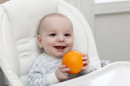 Smiling baby with orange in a highchair photo