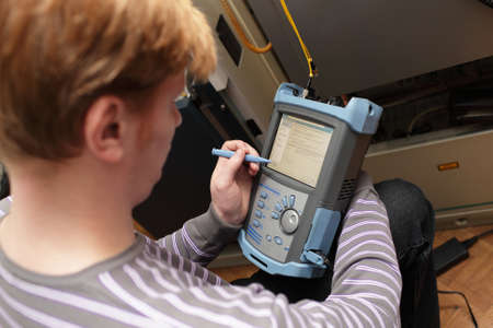 The engineer setting fibre optic reflectometer at a telecom site photo