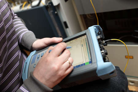 A maintenance engineer measuring fibre optic at a telecom site photo