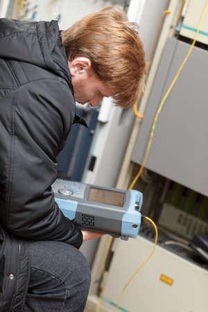 The maintenance engineer holding fibre optic analyzer at a telecom site photo