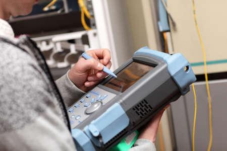 The maintenance technician measuring fibre optic in telecom site photo
