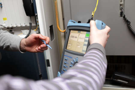 A maintenance technicians with reflectometer at a telecom site Stockfoto