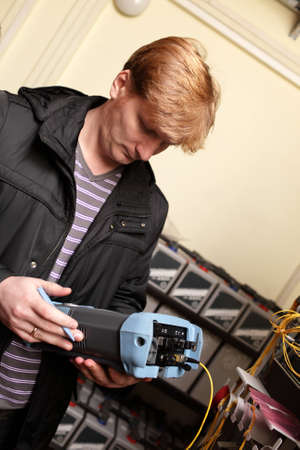 The technician looking at a reflectometer in a telecom site photo