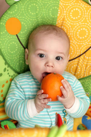 A child biting orange in seesaw at home photo