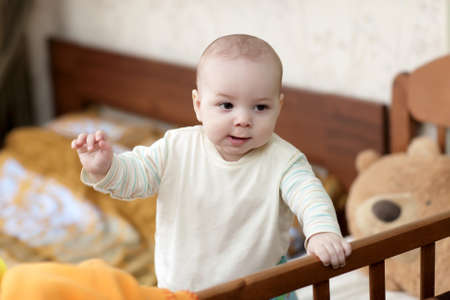 A kid standing in a wooden cot at home Stock Photo - 13101263