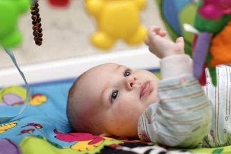 sonaja: Un niño acostado en una camilla de jugar en casa Foto de archivo