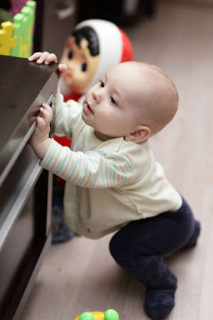The curious kid mounting on a cupboard at home photo