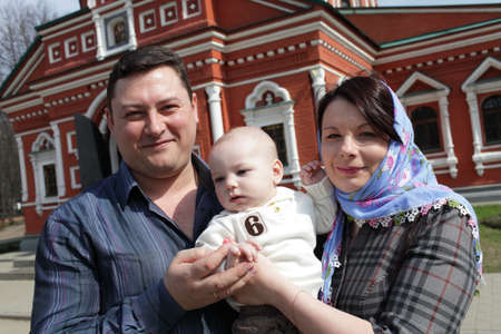 The parents holding child by russian orthodox church Stock Photo - 13525558